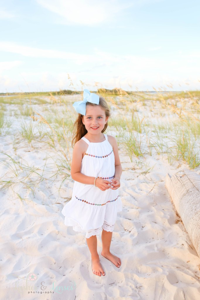 Pre-School age little girl holding a sea shell with the sand dunes behind her at Johnsons Beach in Perdido Key Florida