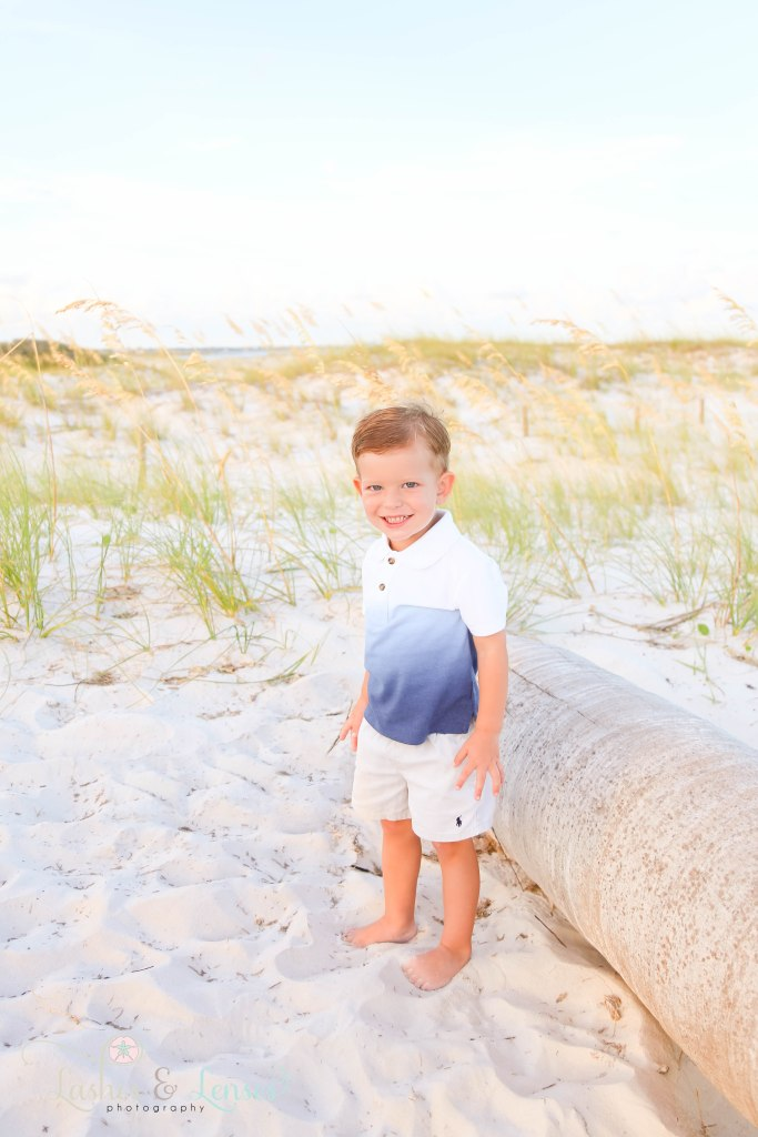 Toddler boy smiling right at the camera and standing next to a washed up palm tree with the sea oats behind him at Johnsons Beach in Perdido Key Florida