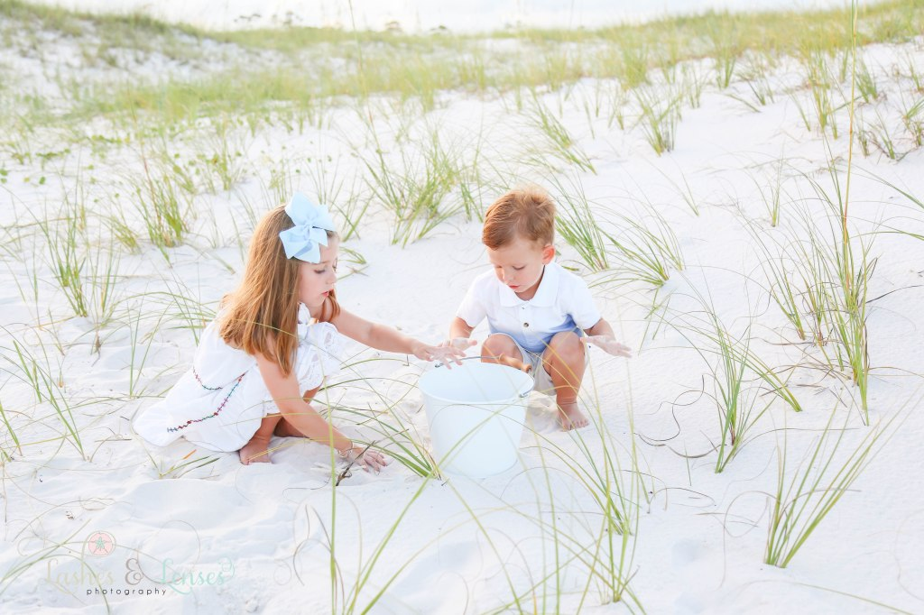 Brother and sister sitting in the sand and playing with a sand bucket at Johnsons Beach in Perdido Key Florida
