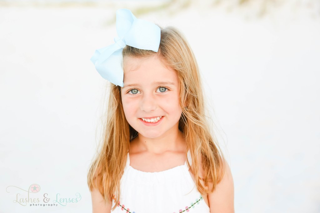 Close up photo of bright blue eyed little film with big blue bow in her hair at Johnsons Beach in Perdido Key Florida