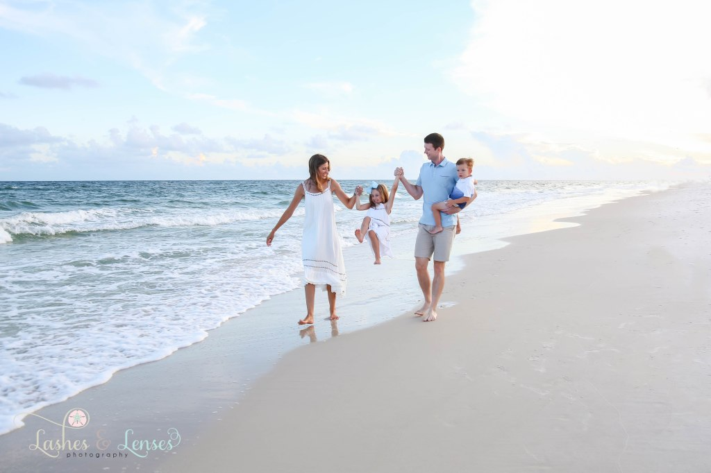 Mom and Dad swinging daughter between them and walking along side the water, dad is holding toddler boy at Johnsons Beach in Perdido Key Florida