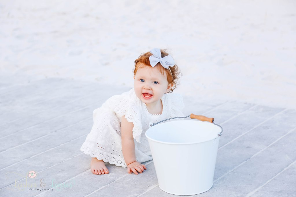 Baby girl with bright red hair and blue eyes playing on the boardwalk with a sand bucket at Johnsons Beach in Perdido Key Florida