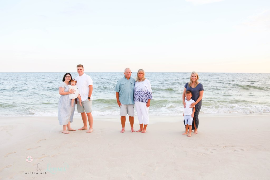 Family standing in their family units at the edge of the water at Johnsons Beach in Perdido Key Florida