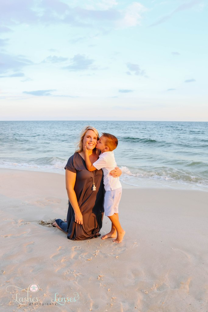 Mom kneeling in the sand with son kissing her on the cheek at Johnsons Beach in Perdido Key Florida