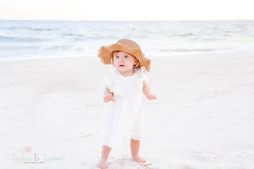 Young toddler girl with a large sun hat standing next the water at Johnsons Beach in Perdido Key Florida