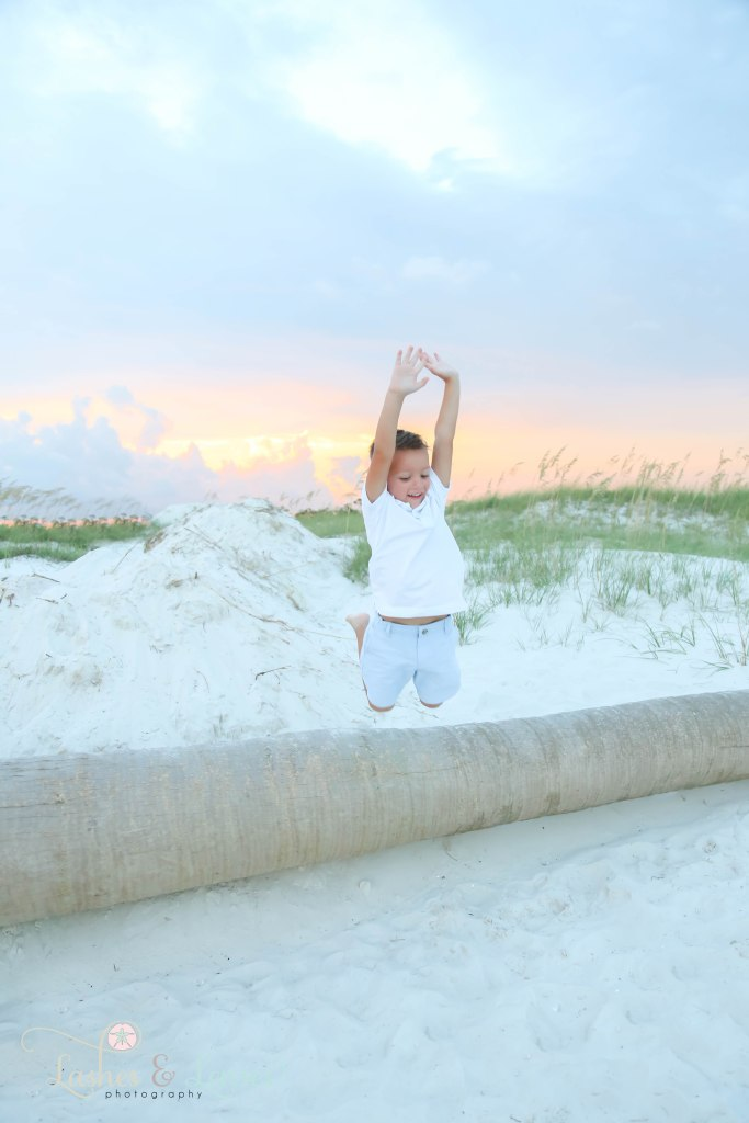 Young boy jumping off and a washed up palm tree at Johnsons Beach in Perdido Key Florida