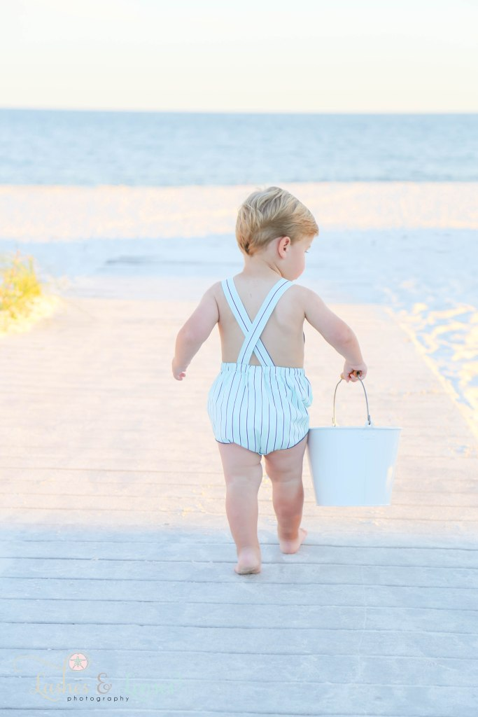 Toddler boy walking down the boardwalk while holding a sand bucket at Johnsons Beach in Perdido Key Florida