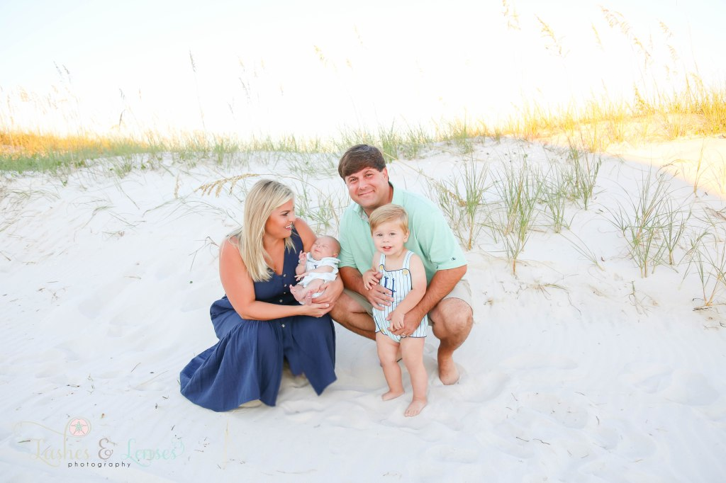 Mom and Dad crouching down with mom holding new born and dad hugging toddler boy with the sand dunes behind them at Johnsons Beach in Perdido Key Florida