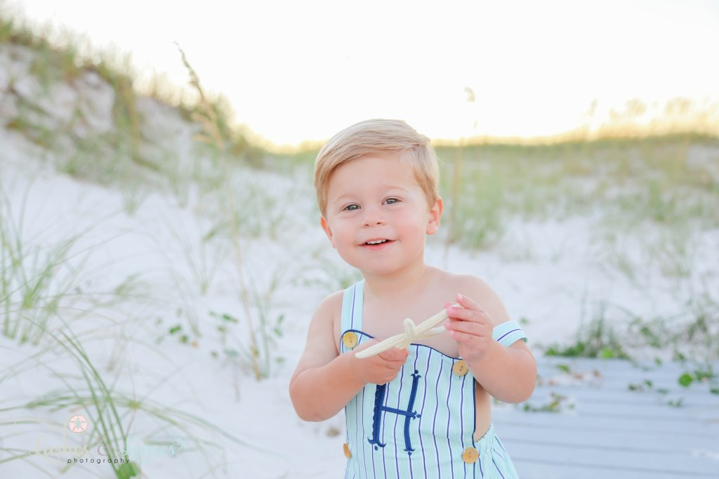 Close up photo of little boy holding a starfish with the sand dunes behind him at Johnsons Beach in Perdido Key Florida