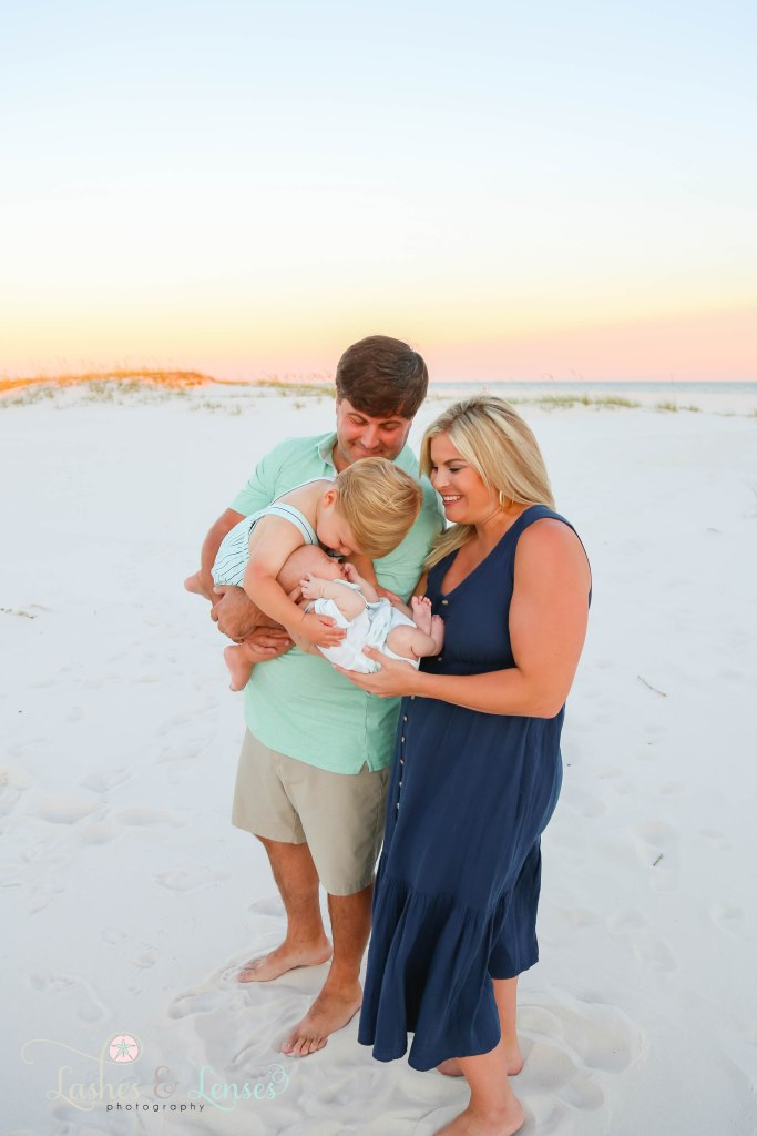 Dad holding toddler brother who is kissing his baby brother who mom is holding at Johnsons Beach in Perdido Key Florida