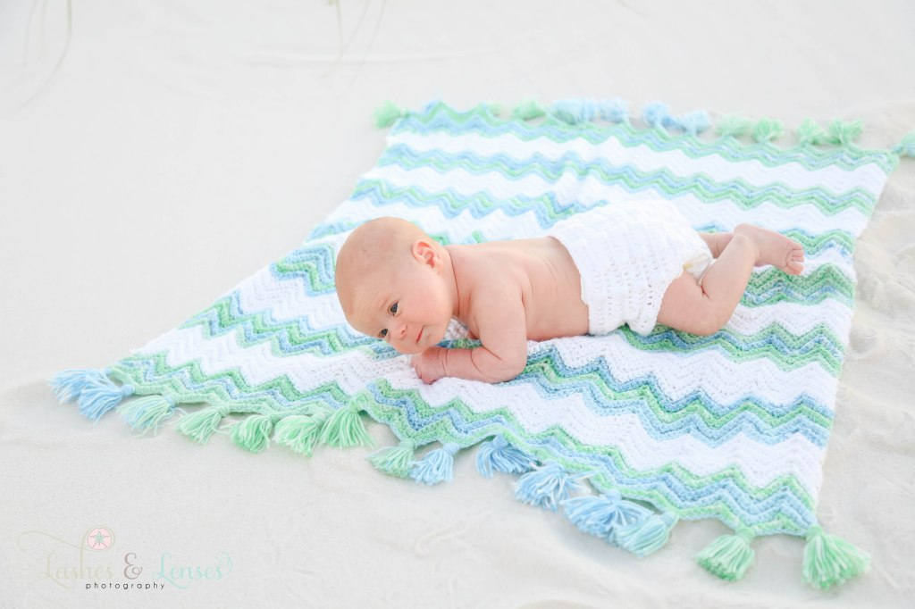 Newborn boy on a crocheted blanket with a hand knit diaper cover on, laying in the sand at Johnsons Beach in Perdido Key Florida