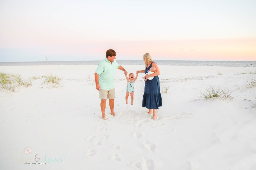 Mom and dad swinging toddler son with the water behind them, mom is holding new born son at Johnsons Beach in Perdido Key Florida