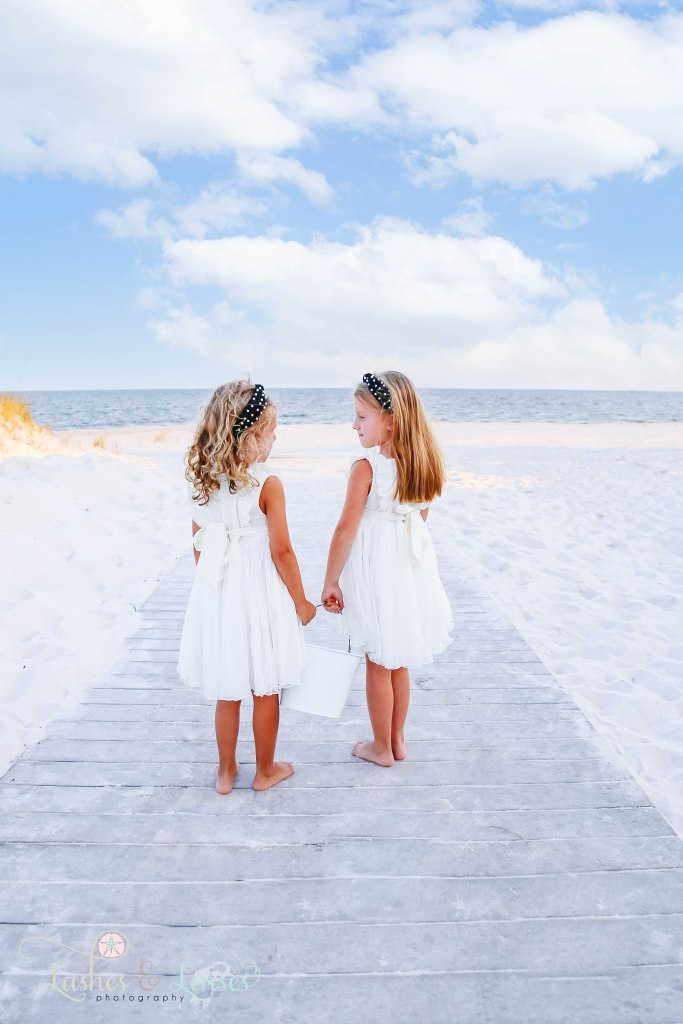 Sisters looking at each other with their backs to the camera and walking down the boardwalk at Johnsons Beach in Perdido Key Florida