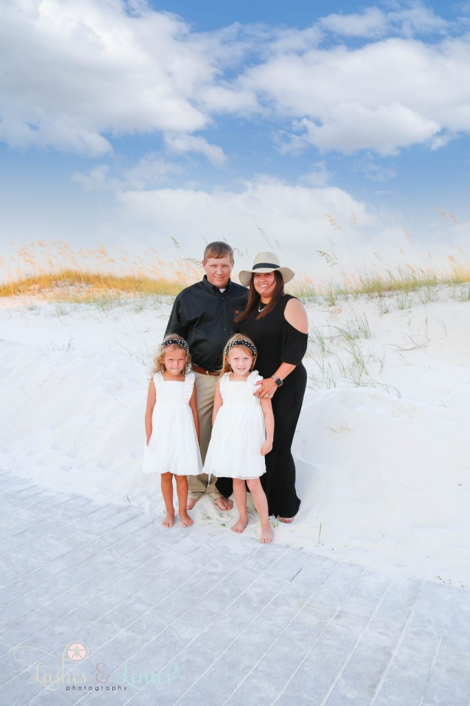 Dad, Mom and their two daughters standing in the sand right off the boardwalk at Johnsons Beach in Perdido Key Florida