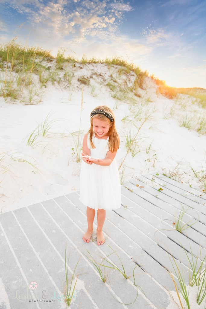 Little girl looking down at a starfish in her hands with the sand dunes at Johnsons Beach in Perdido Key Florida