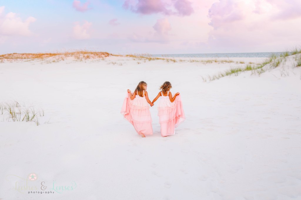 Two sisters in long pink princess dresses walking in the sand at Johnsons Beach in Perdido Key Florida