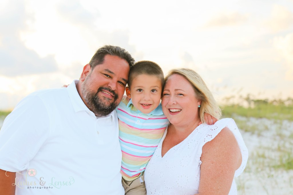 Mom and dad hugging their son in between them with the golden sunlight behind them at Johnsons Beach in Perdido Key Florida