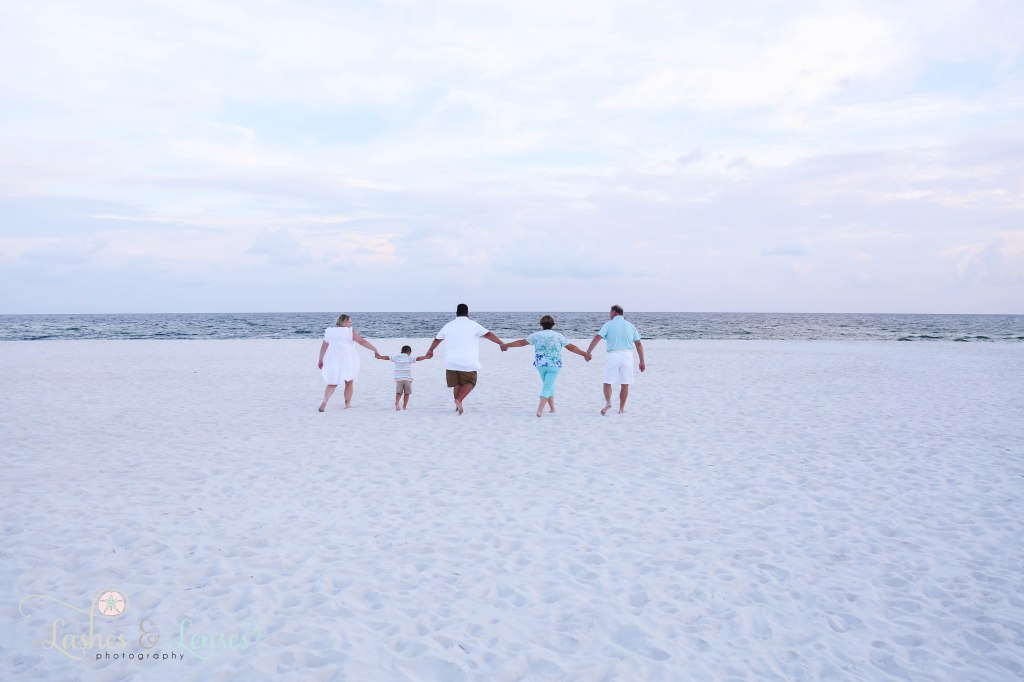 Family walking hand in hand towards the water at Johnsons Beach in Perdido Key Florida