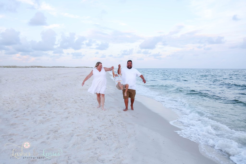 Mom and Dad swinging their son in between them as they walk next to the waters edge at Johnsons Beach in Perdido Key Florida