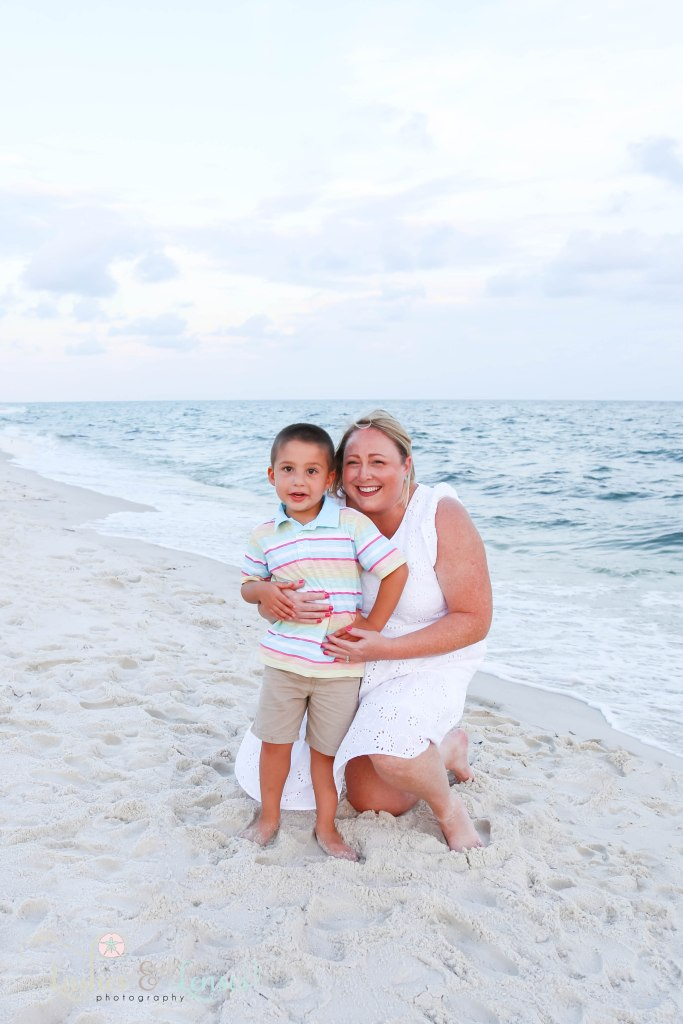 Mom kneeling in the sand next to the water with her toddler son at Johnsons Beach in Perdido Key Florida