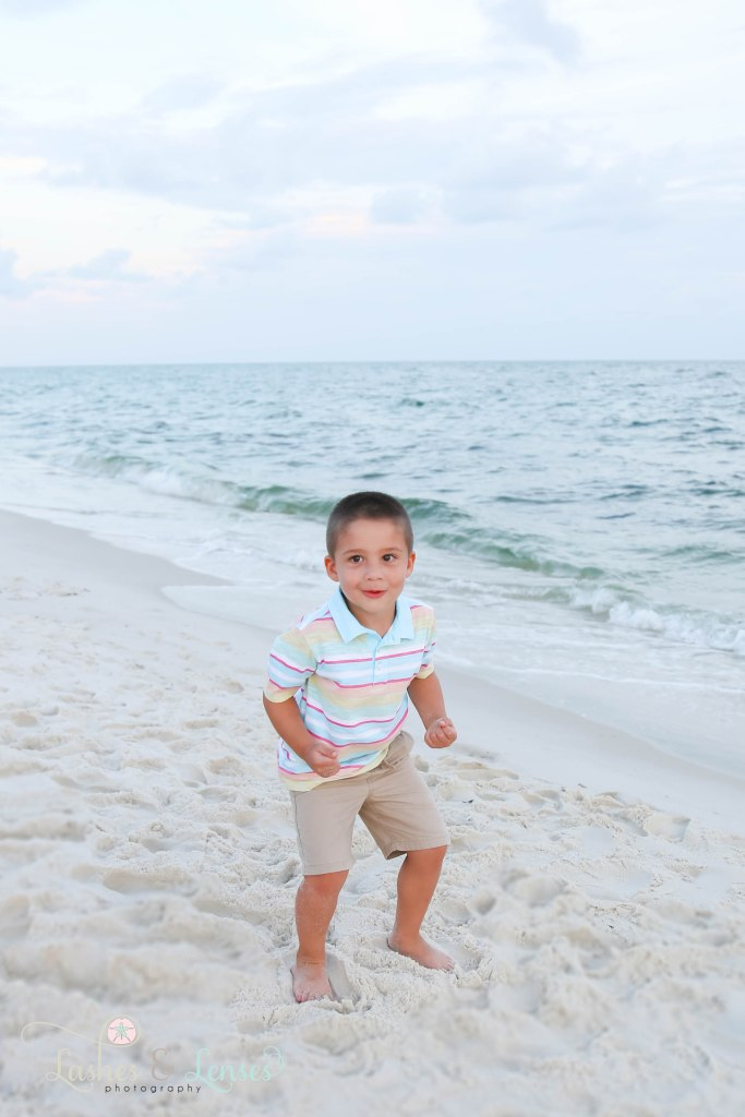 Little boy getting ready to jump for joy next to the waters edge at Johnsons Beach in Perdido Key Florida