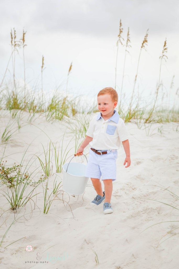 Little boy walking down sand hill and holding a pail at Johnsons Beach in Perdido Key Florida