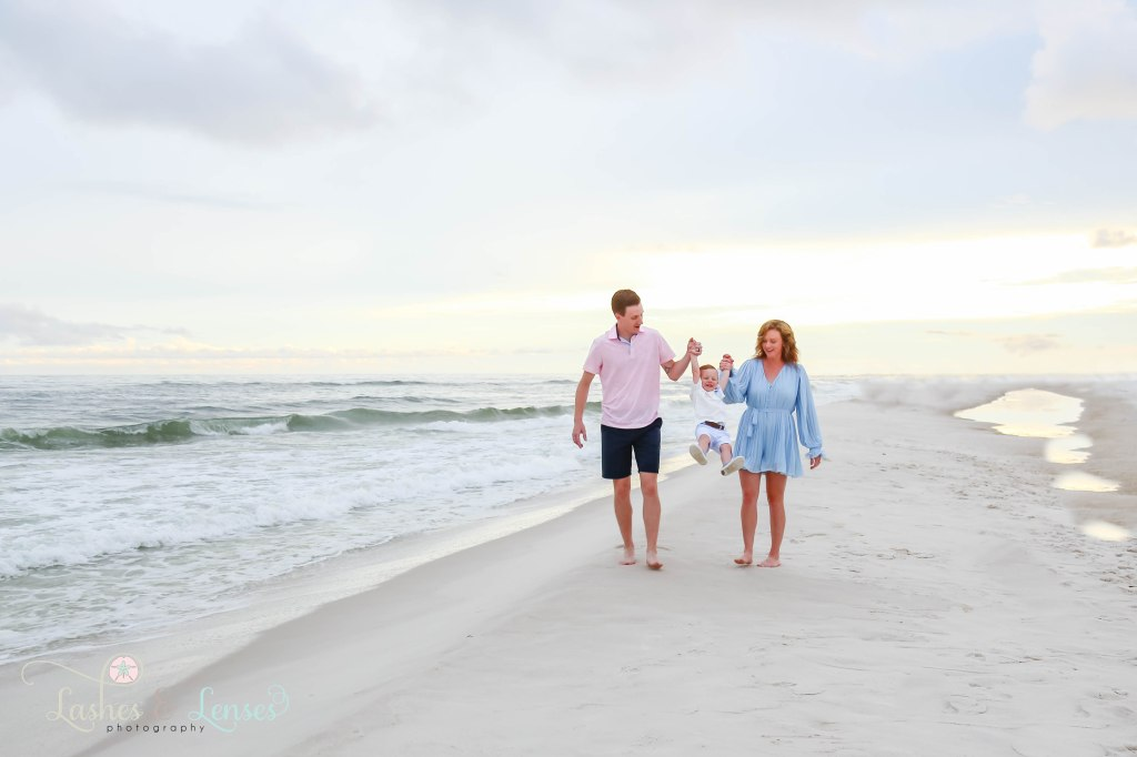 Mom and Dad swinging their toddler son by the hands and walking along the waters edge at Johnsons Beach in Perdido Key Florida