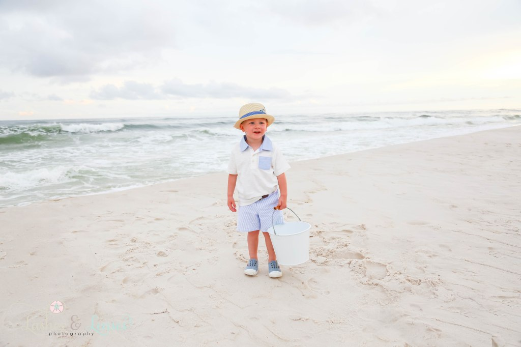 Little boy in sun hat standing on the sand hill next to the water and holding a sand bucket at Johnsons Beach in Perdido Key Florida