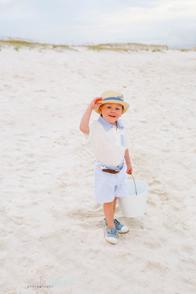 Little boy tipping his hat to the camera at Johnsons Beach in Perdido Key Florida