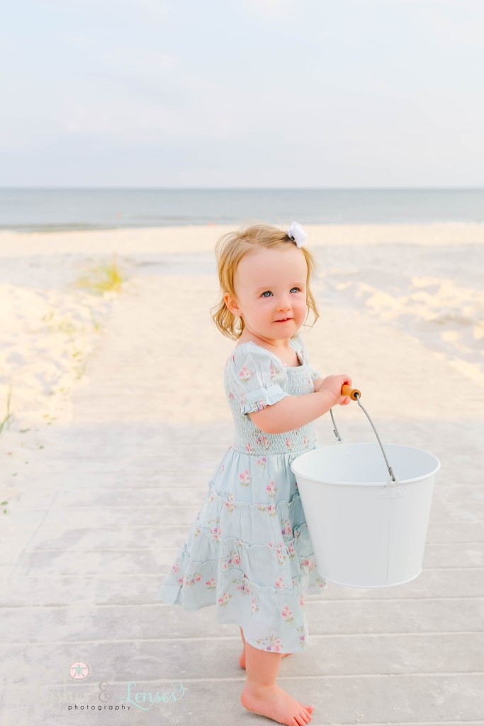 Toddler girl holding sand bucket and standing on boardwalk with the water behind her at Johnsons Beach in Perdido Key Florida