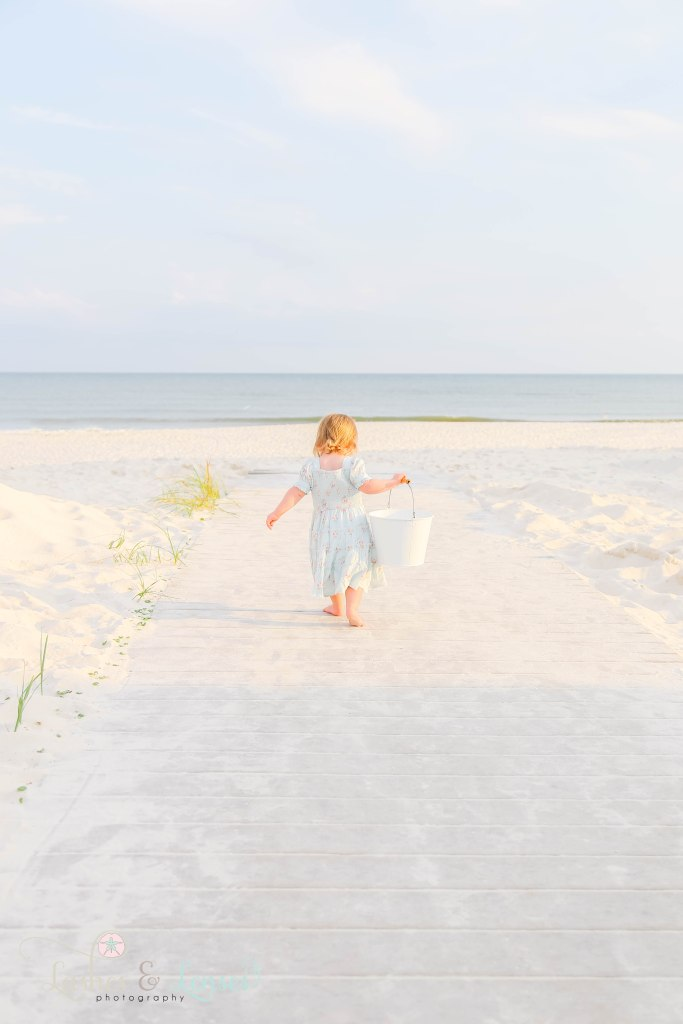 Toddler girl walking down boardwalk with her back to the camera and holding a sand bucket