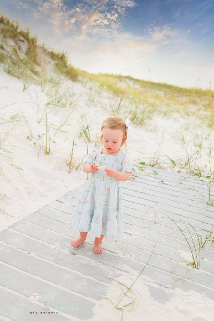 Toddler girl standing on a washed up boardwalk and holding a starfish at Johnsons Beach in Perdido Key Florida