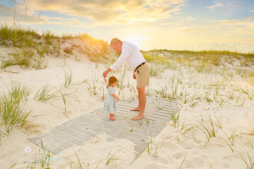 Daddy twirling his daughter around and dancing with her with the sunset behind them at Johnsons Beach in Perdido Key Florida