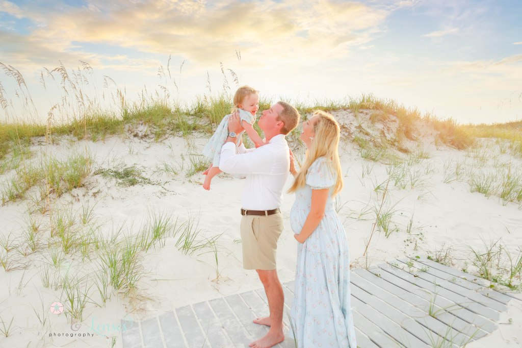 Dad holding up toddle girl and kissing her with mom holding her pregnant belly and laughing at them at Johnsons Beach in Perdido Key Florida