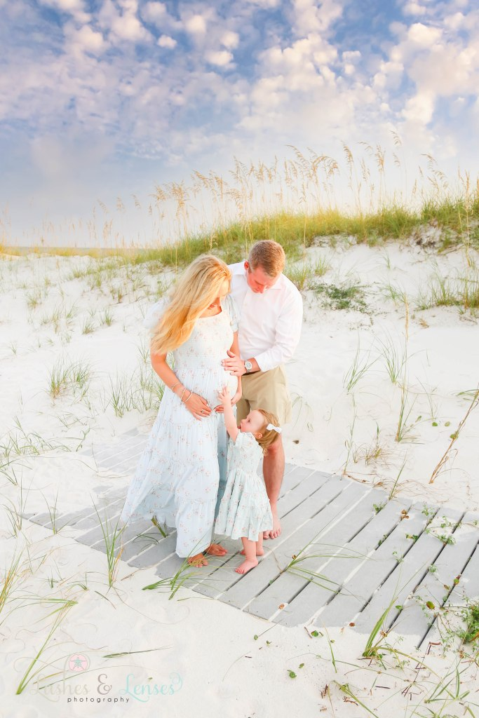 Husband holding pregnant wife's belly and toddler daughter showing her baby brother still in mommy's tummy her starfish at Johnsons Beach in Perdido Key Florida