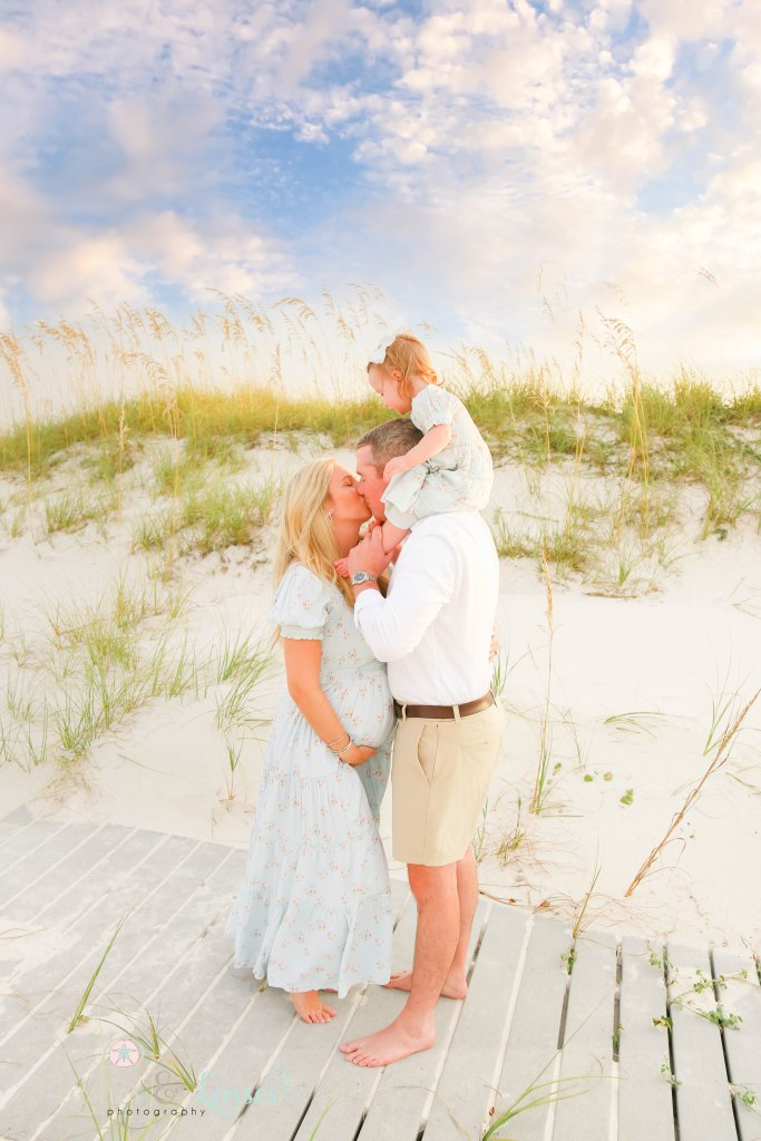 Husband and wife kissing with toddler daughter sitting on dads shoulders with mom holding her pregnant belly at Johnsons Beach in Perdido Key Florida
