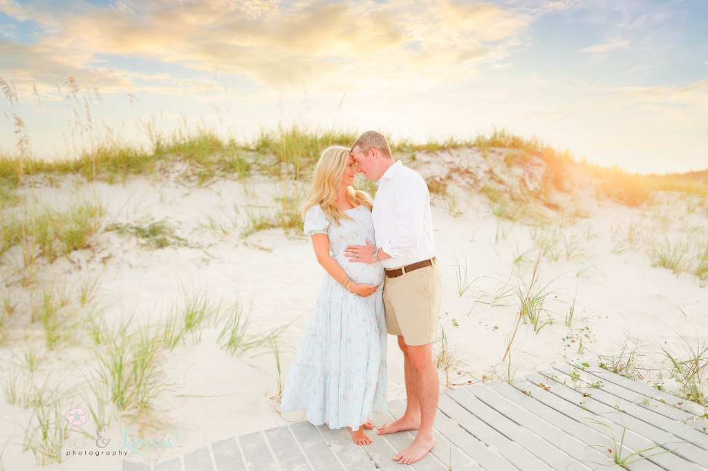 Husband and wife rubbing foreheads and holding moms pregnant belly at Johnsons Beach in Perdido Key Florida