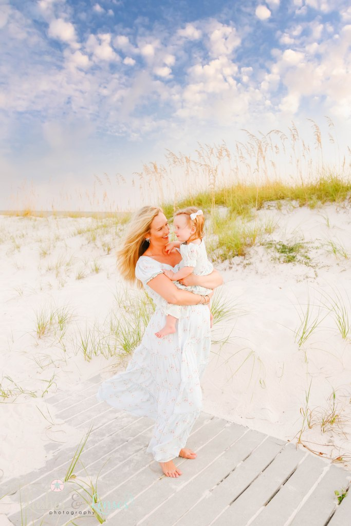 Pregnant Mom holding her toddler daughter and looking at her at Johnsons Beach in Perdido Key Florida