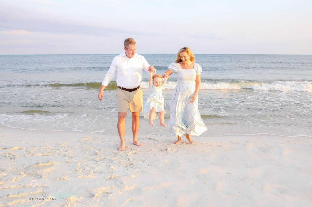 Mom and Dad swinging their toddler daughter in between them at the waters edge at Johnsons Beach in Perdido Key Florida