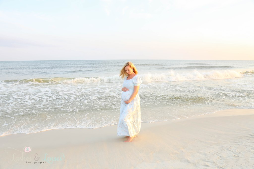 Pregnant woman holding her belly and look down at it and standing at the waters edge at Johnsons Beach in Perdido Key Florida