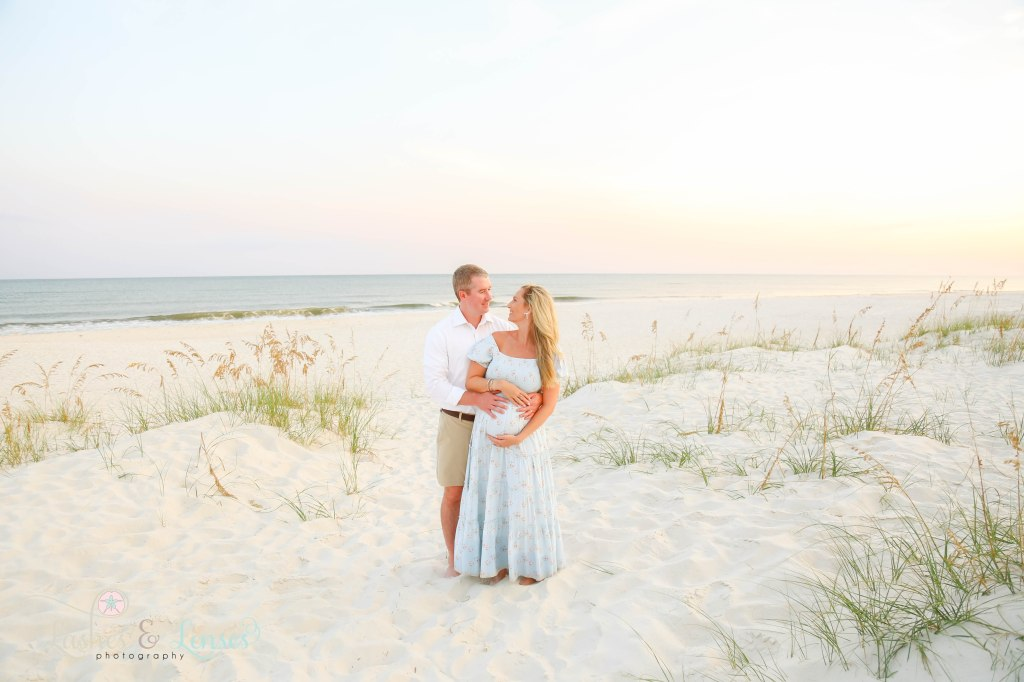 Husband hugging wife from behind and they both have their hands on wife's belly with the sea oats and water behind them at Johnsons Beach in Perdido Key Florida