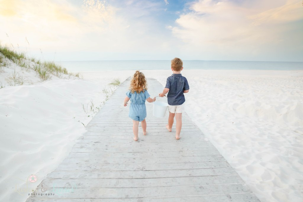 Brother and sister walking down the boardwalk towards the water and holding a bucket in between them at Johnsons Beach in Perdido Key Florida
