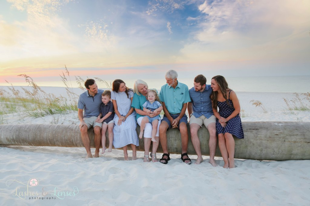 Large extended family sitting on a washed up palm tree and looking at granddaughter at Johnsons Beach in Perdido Key Florida