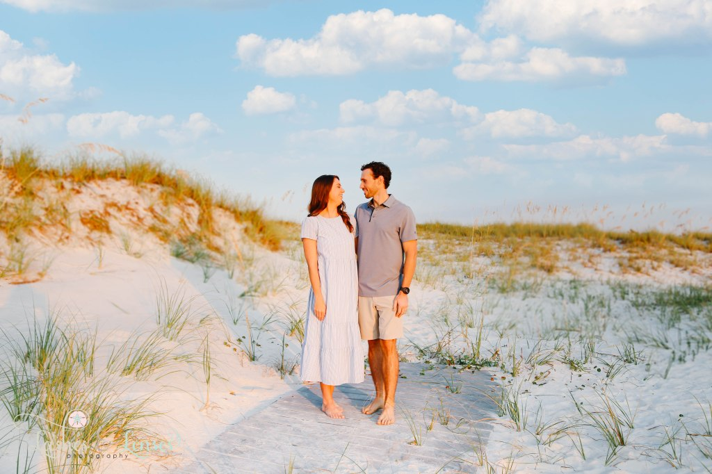 Husband and wife looking at each other as the sun rises in front of them at Johnsons Beach in Perdido Key Florida