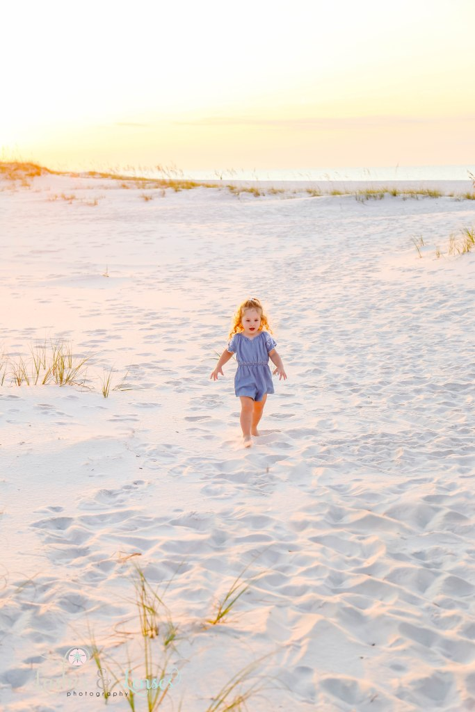 Little girl running and playing in the sand with the sunrise behind her at Johnsons Beach in Perdido Key Florida