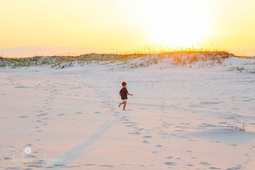 Little boy running and playing in the sand with the sunrise behind him at Johnsons Beach in Perdido Key Florida