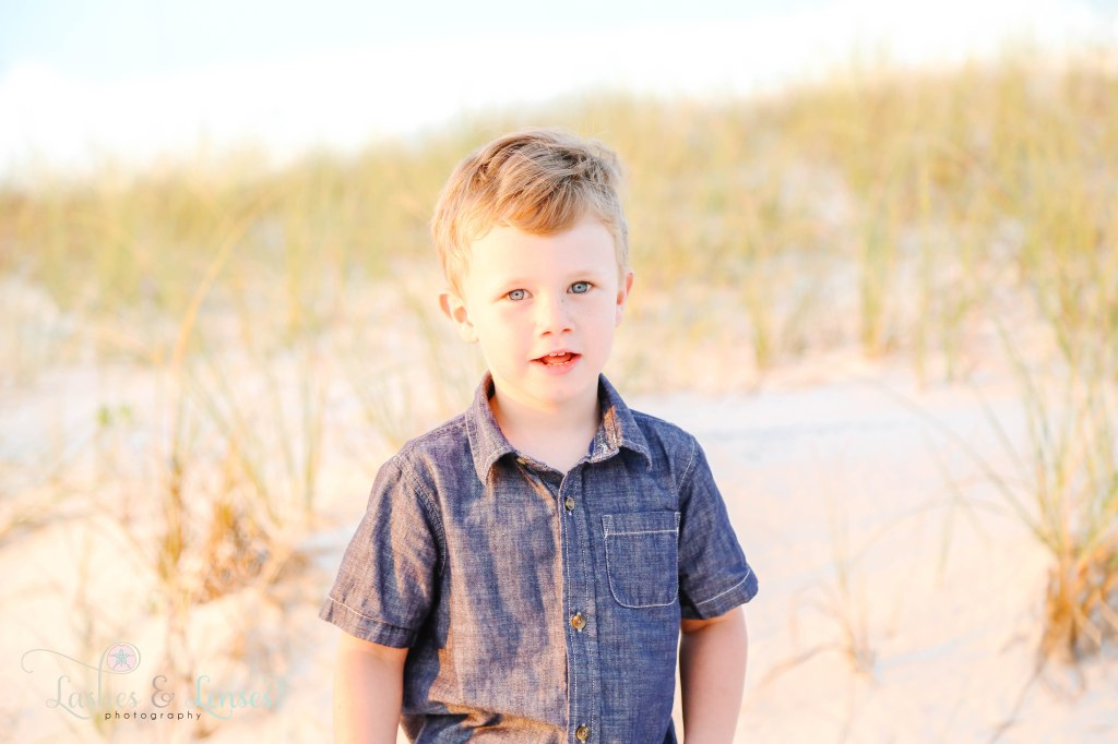 Close up photo of little boy with the golden sea oats behind him at Johnsons Beach in Perdido Key Florida