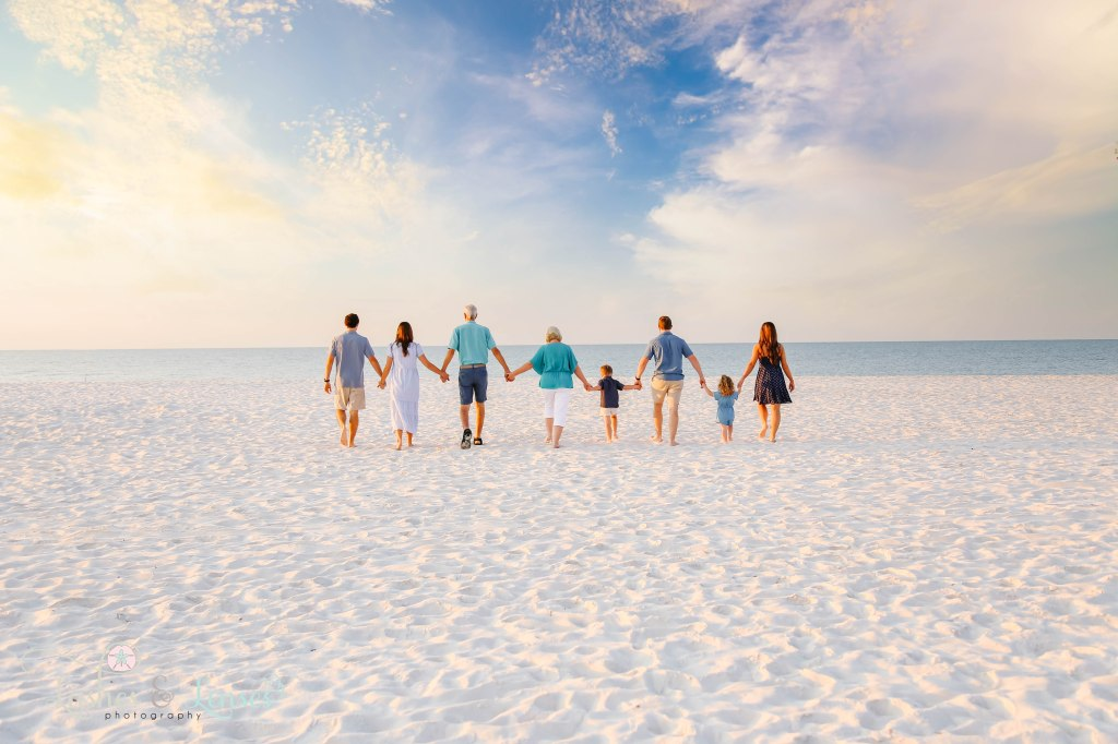 Extended family all holding hands and walking down to the water at Johnsons Beach in Perdido Key Florida