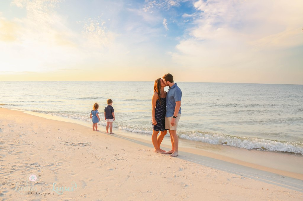 Mom and Dad kissing at the waters edge with their kids behind them looking at the water at Johnsons Beach in Perdido Key Florida