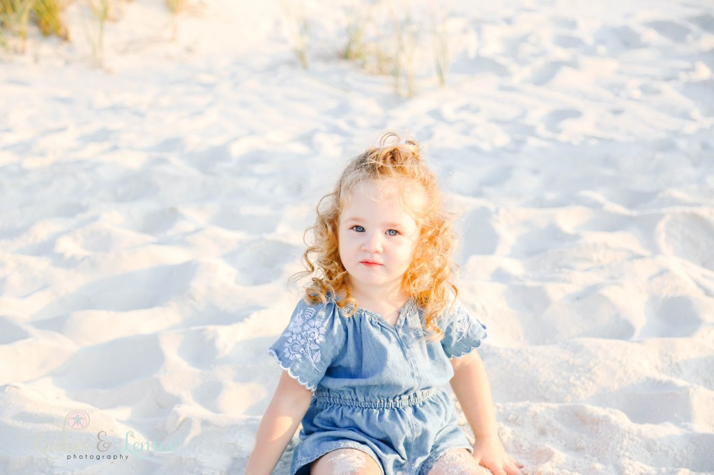 Close up photo of little girl sitting in the pure white sand at Johnsons Beach in Perdido Key Florida